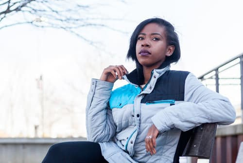 Woman sitting on bench thinking about taking Naltrexone for her addiction
