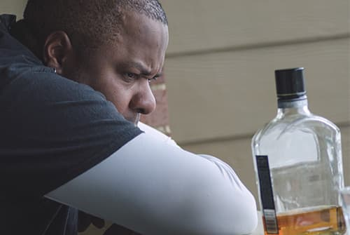 Man looking intently at bottle of alcohol, struggling with alcoholism