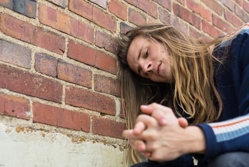 Man portraying an addict leaning against brick wall outside