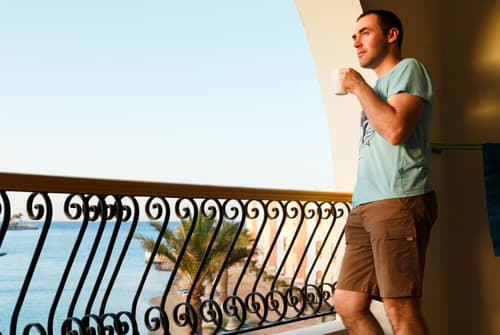 Man standing on balcony overlooking ocean portraying addict in luxury rehab facility