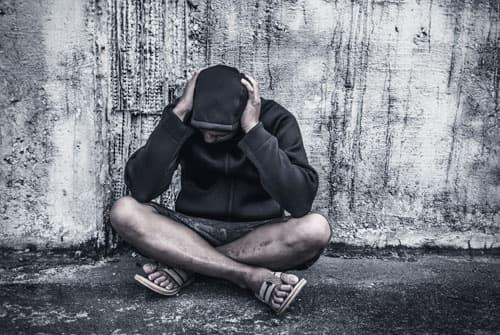 upset heroin addict sitting on ground