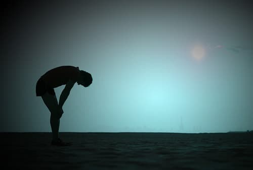 silhouette of man tired with hands on knees