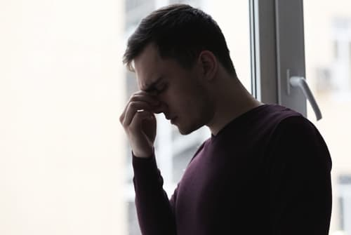 stressed man touches face by window