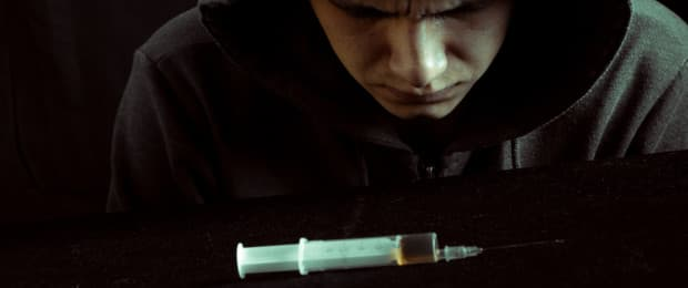 man looking at heroin needle